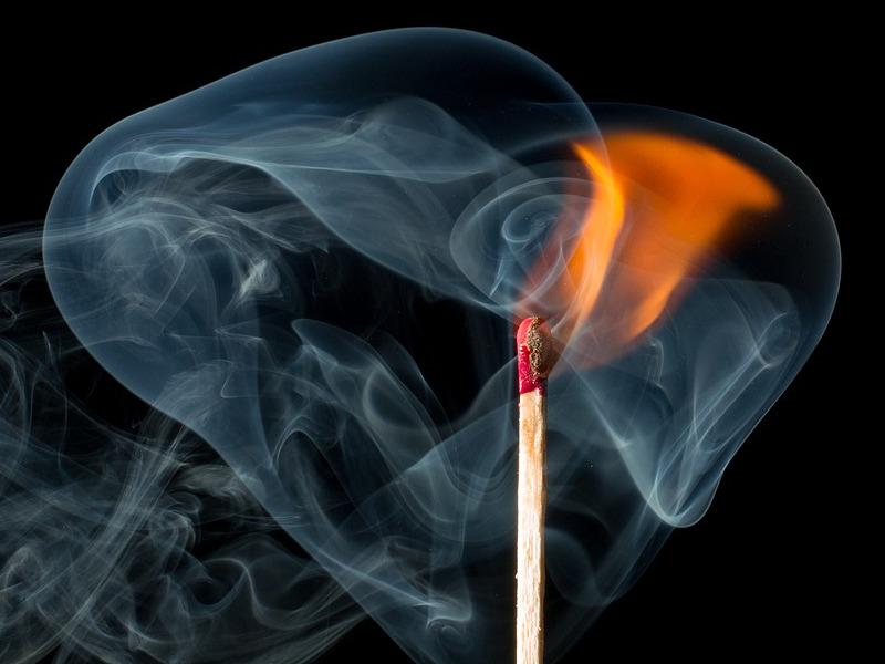 płomień zapałki otoczony dymem
